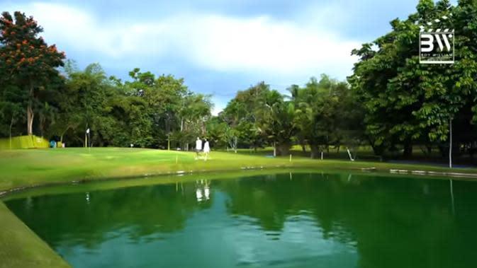 Tampak halaman belakang sangat luas dan hijau. Danau, banyak pohon besar, rumput yang rapi warna hijau menambah asri rumah Ovi. (Youtube/Boy William)