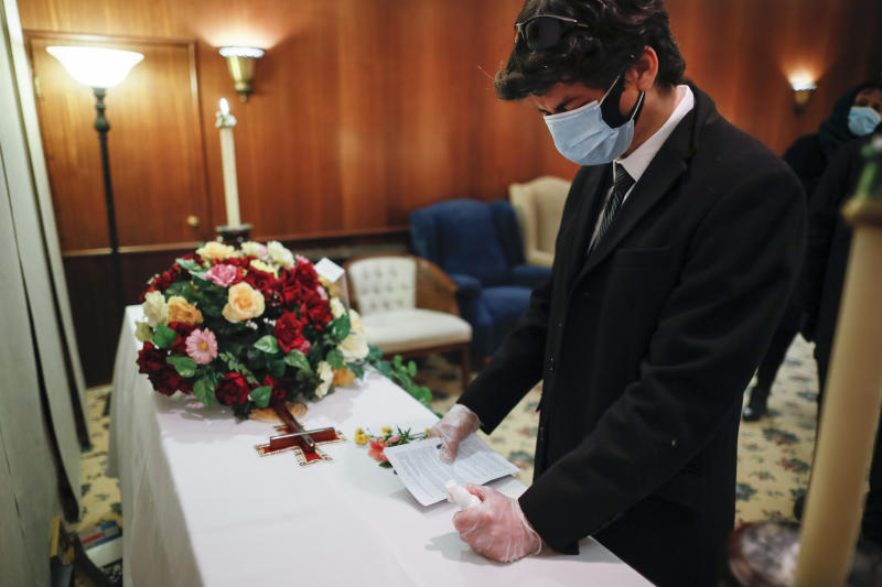 Leonardo Cabana cries over the casket of his father Hector Cabana who died of COVID-19 after a funeral home service given by Fabian Arias, a Lutheran pastor with Saint Peter's Church in Manhattan, Monday, May 11, 2020, in the Brooklyn borough of New York. (AP Photo/John Minchillo)
