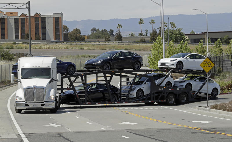 A truck hauling new Tesla vehicles leaves the Tesla factory plant on Monday, May 11, 2020, in Fremont, Calif. The parking lot was nearly full at Tesla's California electric car factory Monday, an indication that the company could be resuming production in defiance of an order from county health authorities. (AP Photo/Ben Margot)