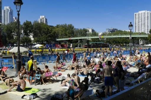 A crowded outdoor swimming pool on a canal in central Paris as people seek relief from the heat