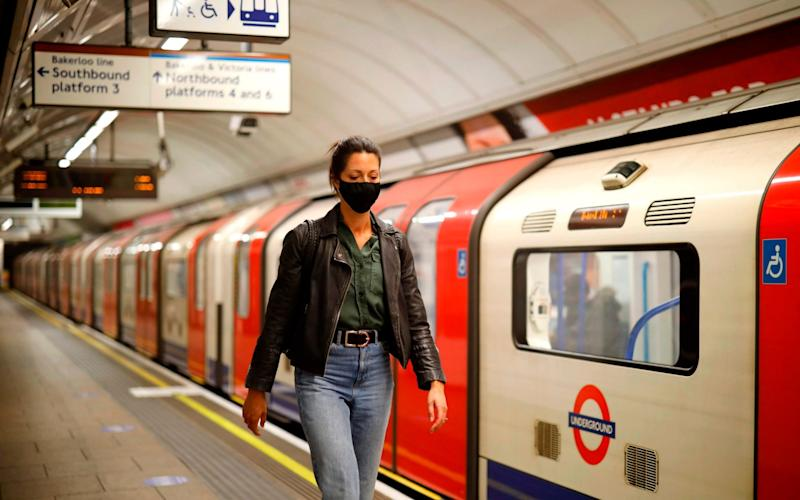A commuter wears a face mask as she disembarks at a tube station in London - Tolga Akmen/AFP