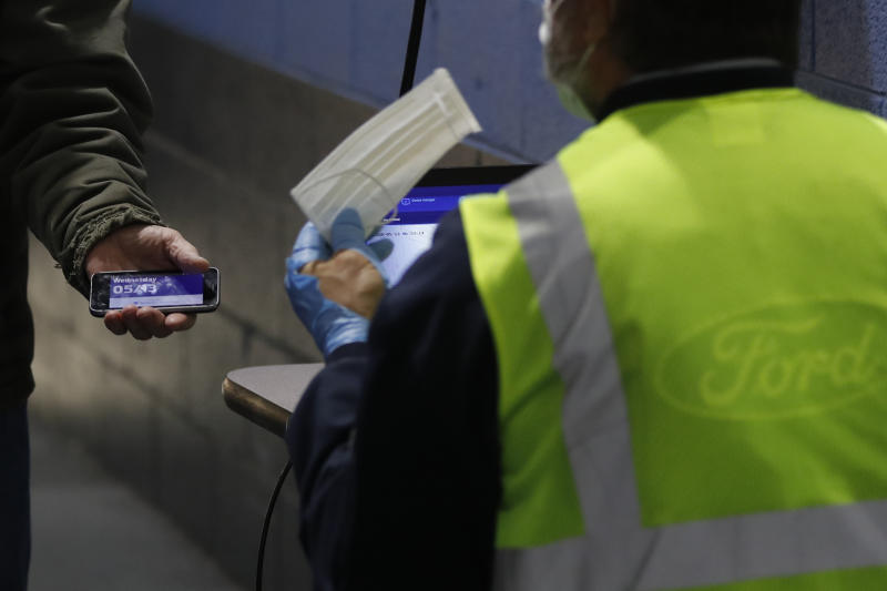 A Ford employee, left, shows his COVID-19 daily survey pass and is given a face mask as he enters the Ford Rawsonville plant, Wednesday, May 13, 2020 in Ypsilanti Township, Mich. The plant was converted into a ventilator factory, as hospitals battling the coronavirus report shortages of the life-saving devices. The company has promised to deliver 50,000 by July 4. Ford and other automakers are preparing for the reopening of their plants next week. Factories must adopt measures to protect their workers, including daily entry screening and, once they are available, the use of no-touch thermometers. Those measures already are in effect at Rawsonville. (AP Photo/Carlos Osorio)