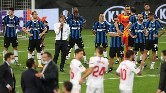 Pemain Inter Milan tampak lesu menyaksikan pemain Sevilla merayakan gelar juara Liga Europa 2019/2020 di Stadion RheinEenergie, Sabtu (22/8/2020) dini hari WIB. Inter Milan kalah 2-3 atas Sevilla. (AFP/Lars Baron/pool)