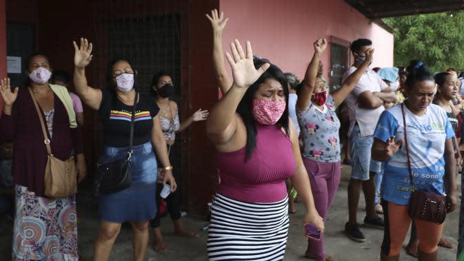 Kerabat mengangkat tangan mereka dalam doa saat para narapidana melakukan protes di Penjara Puraquequara, Manaus, Brasil, Sabtu (2/5/2020). Narapidana memprotes kondisi buruk dan pemberlakuan pembatasan kunjungan keluarga untuk mencegah penyebaran virus corona COVID-19. (AP Photo/Edmar Barros)