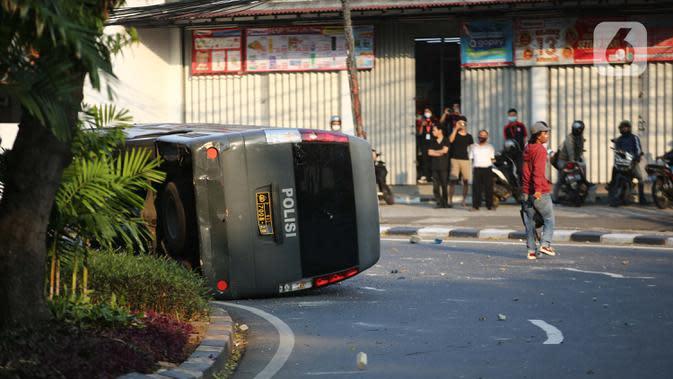 Sebuah mobil polisi dirusak massa saat bentrok di kawasan Pejompongan, Jakarta, Rabu (7/10/2020). (Liputan6.com/Faizal Fanani)