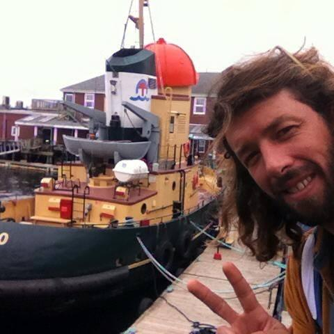 Sean McKinnon poses in front of a boat while making a peace symbol with his hand in 2016.