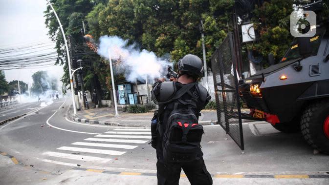 Anggota brimob menembakan gas air mata saat memukul mundur massa di kawasan Tanah Abang, Jakarta, Selasa (13/10/2020). Hingga menjelang magribh massa masih melakukan perlawan di kawasaan tersebut. (Liputan6.com/Faizal Fanani)