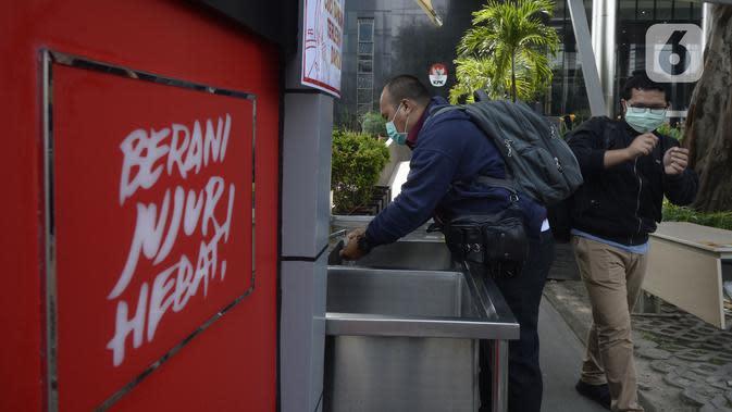 Tamu mencuci tangan sebelum memasuki Gedung KPK, Jakarta, Senin (30/3/2020). KPK menyediakan fasilitas cuci tangan bagi pengunjung, karyawan, serta petugas keamanan sebelum memasuki gedung guna mencegah penyebaran virus corona COVID-19. (merdeka.com/Dwi Narwoko)