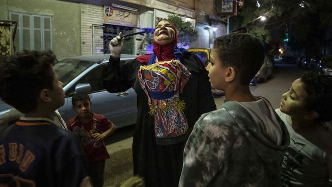Seorang mesaharati Hajja Dalal (46) membangunkan warga untuk sahur saat bulan suci Ramadan di Kairo, Mesir, Rabu (29/4/2020). Mesaharati telah ada selama beberapa generasi dan merupakan tradisi terhormat. (AP Photo/Nariman El-Mofty)