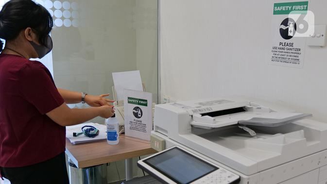 Karyawan menggunakan cairan pembersih tangan setelah menggunakan mesin fotokopi di ruang kantor Suntory Garuda, Jakarta, Senin (8/8/2020). Suntory Garuda menerapkan protokol Kesehatan, salah satunya kapasitas karyawan hanya dibolehkan sebanyak 50 persen. (Liputan6.com/Herman Zakharia)