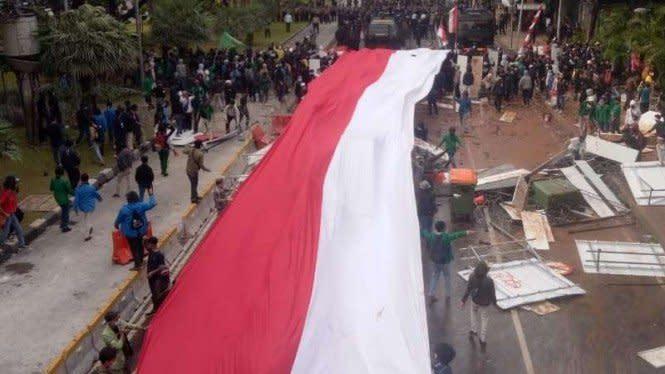 Pendemo Omnibus Law di Patung Kuda Bawa Bendera Merah Putih Raksasa