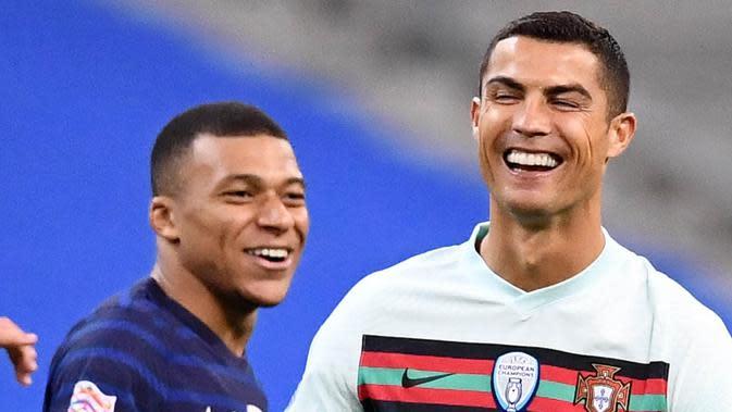 Striker Portugal, Cristiano Ronaldo, tertawa bersama striker Prancis, Kylian Mbappe, pada laga UEFA Nations League di Stadion Stade de France, Senin (12/10/2020). Kedua tim bermain imbang 0-0. (AFP/Franck Fife)
