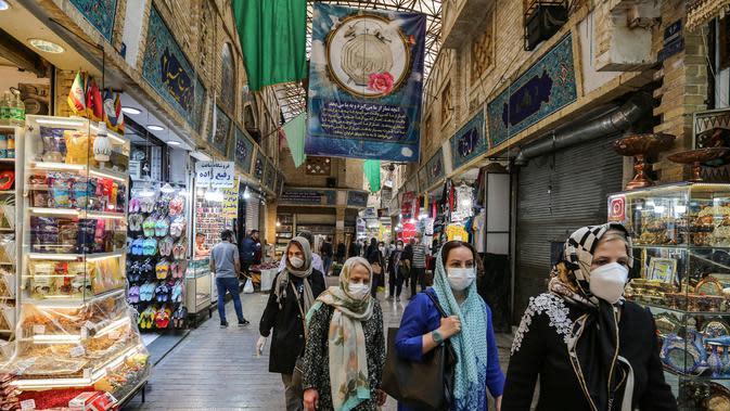 Para pembeli mengenakan masker dan sarung tangan lateks, akibat pandemi coronavirus COVID-19, berjalan di pasar Tajrish selama bulan suci Ramadan di Taheran, Iran (25/4/2020). (AFP/Atta Kenare)