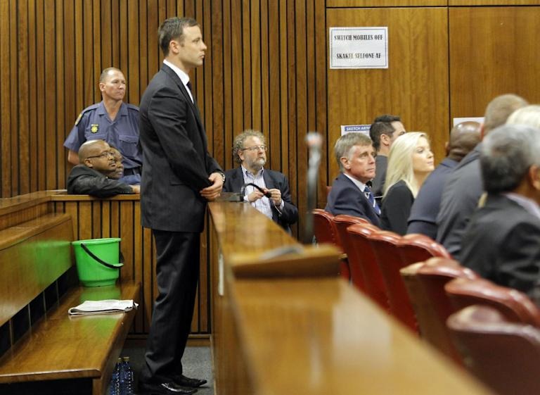 Oscar Pistorius stands in the dock in court in Pretoria, South Africa, Thursday Sept. 11, 2014 for judgement in his murder trail for the shooting death of his girlfriend Reeva Steenkamp on Valentine's Day in 2013. The judge in the Oscar Pistorius murder trial on Thursday read the reasoning behind her upcoming verdict on whether the double-amputee athlete intentionally killed girlfriend Reeva Steenkamp. (AP Photo/Kim Ludbrook, Pool)