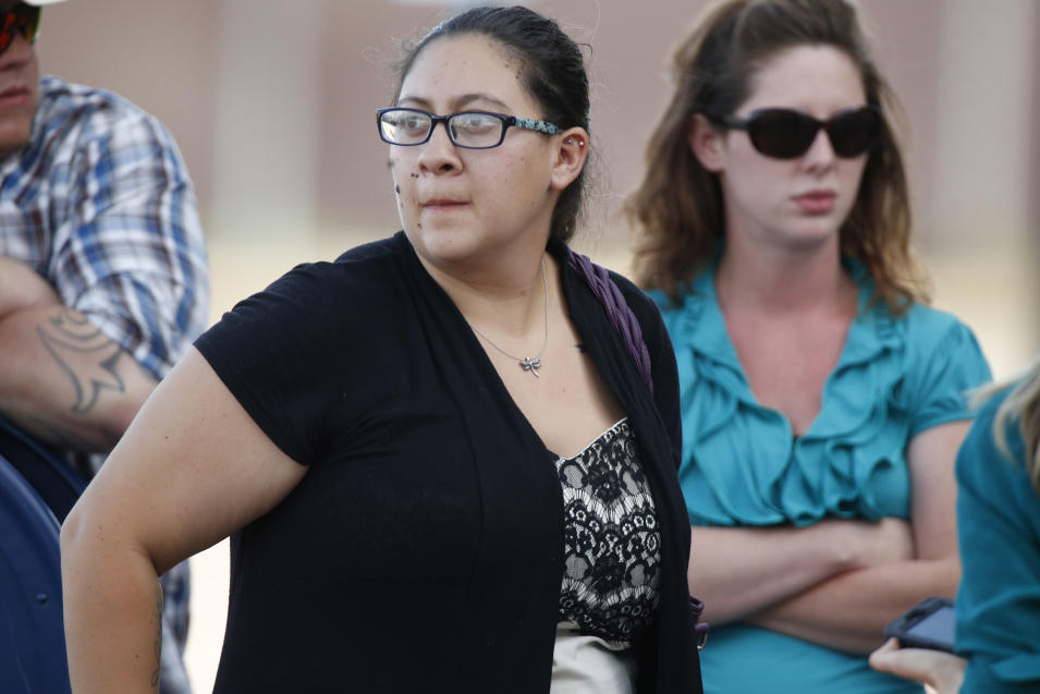 Katie Medley, front, whose husband, Caleb, was severely wounded in the 2012 massacre at an Aurora, Colo., theater, emerges from Arapahoe County Courthouse after jurors convicted shooter James Holmes as the trial concluded Thursday, July 16, 2015, in Centennial, Colo. The 27-year-old Holmes could get the death penalty for the killing spree that left 12 people dead and dozens of others wounded. (AP Photo/David Zalubowski)