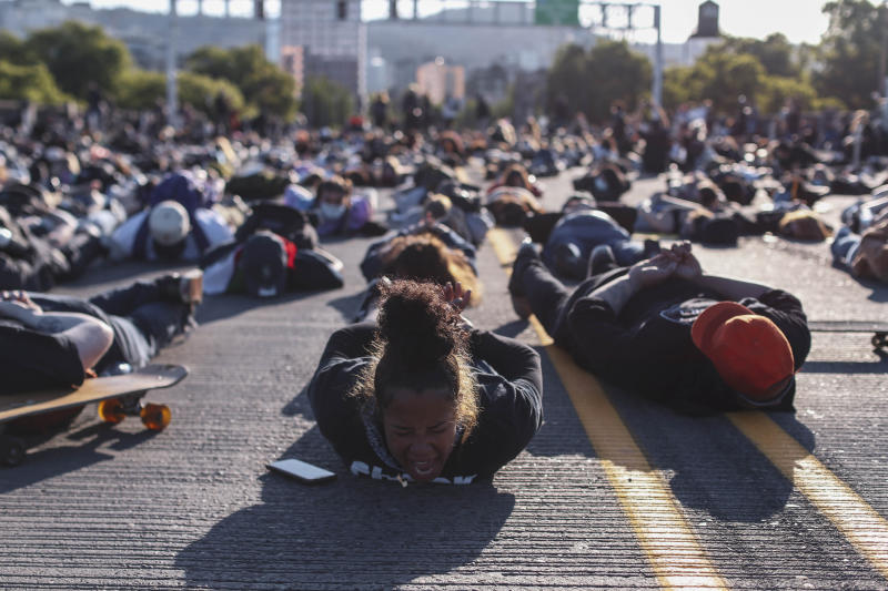 In this Monday, June 1, 2020 photo, protesters prepare to observe nine minutes of silence on the Burnside Bridge in Portland, Ore. Portland will not impose a curfew on Tuesday night for the first time in four days after several thousand demonstrators remained largely peaceful during a march the night before to protest the killing of George Floyd in Minneapolis. (Beth Nakamura/The Oregonian via AP)