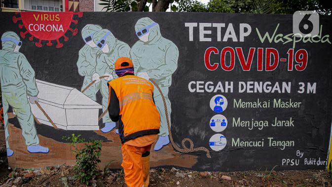 Petugas PPSU Kelurahan Bukit Duri menyelesaikan mural bertema Covid-19 di Jakarta, Selasa (11/8/2020). Mural tersebut untuk mengingatkan warga agar selalu waspada dengan Covid-19 dan mencegahnya dengan 3M (Memakai Masker, Menjaga Jarak dan Mencuci Tangan). (Liputan6.com/Faizal Fanani)