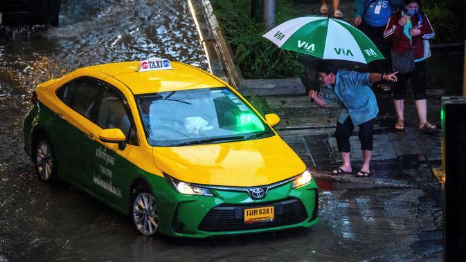 Seorang pejalan kaki menghentikan taksi saat hujan deras di Bangkok (23/9/2020). (AFP/Mladen Antonov)