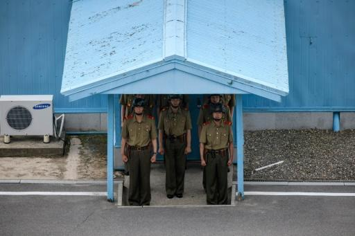 Korean People's Army soldiers stand beneath the entrance to a pavillion before the Military Demarcation Line (MDL) at the truce village of Panmunjom on the North Korean side of the Demilitarized Zone (DMZ) separating North and South Korea
