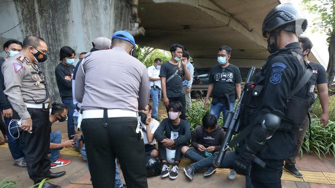 Polisi merazia pelajar yang sedang berkumpul di sekitar Gedung DPR/MPR, Jalan Gatot Subroto, Jakarta, Rabu (7/10/2020). Sejumlah akses jalan menuju lokasi dijaga menyusul adanya aksi demonstrasi kelompok buruh yang menolak UU Omnibus Law Cipta Kerja. (merdeka.com/Imam Buhori)