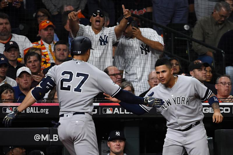 HOUSTON, TX - OCTOBER 12: Giancarlo Stanton #27 of the New York Yankees is greeted by teammate Gleyber Torres #25 after hitting a solo home run in the sixth inning during Game 1 of the ALCS between the New York Yankees and the Houston Astros at Minute Maid Park on Saturday, October 12, 2019 in Houston, Texas. (Photo by Cooper Neill/MLB Photos via Getty Images)