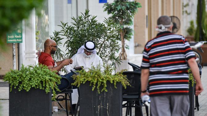 Sejumlah pria duduk di luar sebuah kafe di sepanjang jalan Tahlia di pusat ibukota Arab Saudi, Riyadh (21/6/2020). Pemerintah Arab Saudi mulai membuka kembali kegiatan perekonomian setelah melonggarkan lockdown Covid-19. (AFP Photo/Fayez Nureldine)