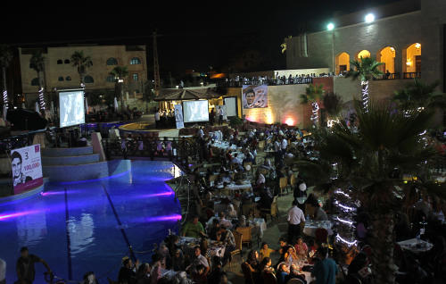 """Palestinians watch the televised performance of Mohammed Assaf, 23, a Palestinian finalist on the Arab Idol talent show, in Gaza City, Friday, June 21, 2013. Assaf, Gazan's powerful voice has propelled him to the final at the """"Arab Idol"""" in a TV talent contest choosing a winner in Beirut on Saturday. He is the first Palestinian to qualify for """"Arab Idol."""" (AP Photo/Adel Hana)"""