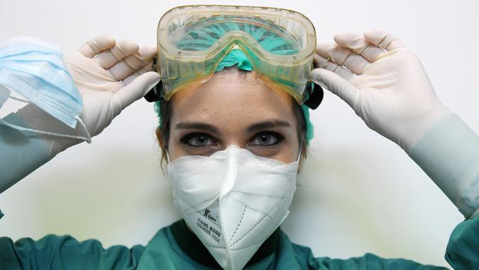 Seorang perawat mengenakan alat pelindung diri (APD) sebelum memasuki ruang perawatan COVID-19 di Rumah Sakit Santo Spirito, Roma, Italia (12/4/2020). Hari Perawat Internasional diperingati di seluruh dunia pada 12 Mei atau bertepatan dengan hari lahir Florence Nightingale. (Xinhua/Alberto Lingria)