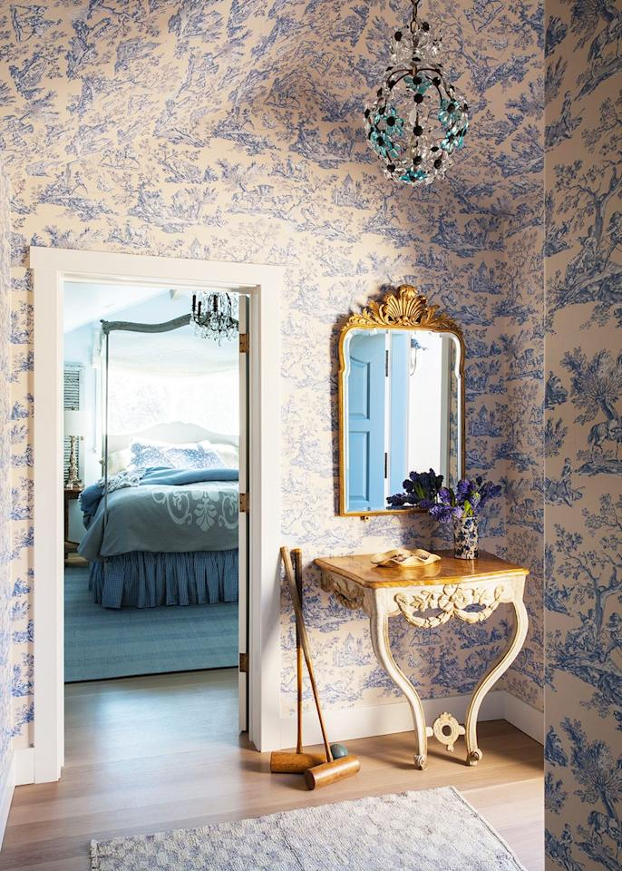 <p>You can't go wrong with a classic blue and white color scheme. Instead of cool whites, opt for creams, and instead of dark wood, go for a blond finish. The toile wallcovering and crystal floral chandelier in this vestibule designed by Heather Hilliard segues into the blue bedroom beyond seamlessly.</p>