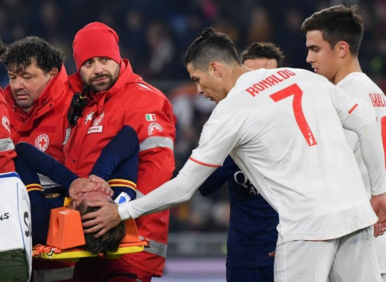 Juventus star Cristiano Ronaldo (r) comforts Nicolo Zaniolo as he is stretchered off the pitch in tears at the Stadio Olimpico