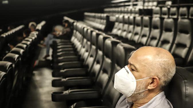 Seorang pria duduk di bioskop