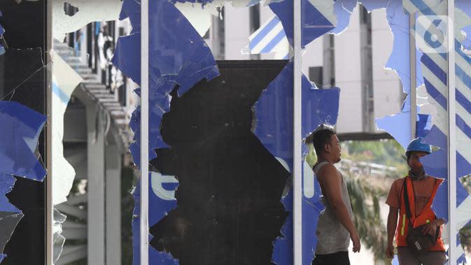 Pekerja berada diantara sisa pecahan kaca di halte transjakarta Senen, Jakarta, Jumat (9/10/2020). Unjuk rasa menentang disahkannya Omnibus Law UU Cipta Kerja berujung aksi anarkis merusak berbagai fasilitas umum pada Kamis malam (8/10). (Liputan6.com/Helmi Fithriansyah)