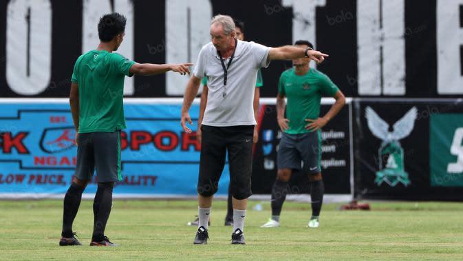 Alfred Riedl saat menjelaskan strategi menyerang kepada Bayu Pradana pada sesi latihan di Stadion Maguwoharjo, Sleman, Jumat (07/10/2016). (Bola.com/Nicklas Hanoatubun)