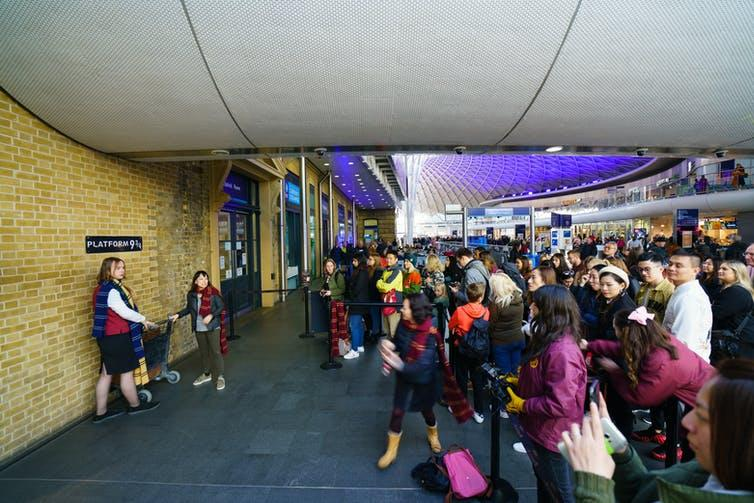 Fans wait for a photo opportunity at the Harry Potter platform 9 3/4 at King's Cross Station, London