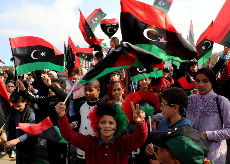 People wave Libyan flags as they gather during celebrations commemorating the 9th anniversary of the revolution at Martyrs' Square in Tripoli