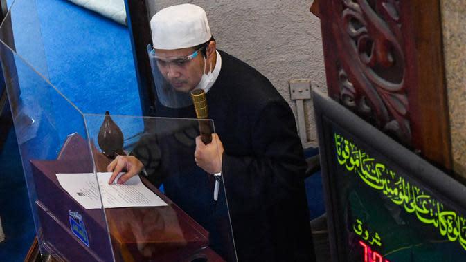 Seorang imam mengenakan pelindung wajah saat khotbah salat Jumat usai pencabutan pembatasan Covid-19 di Masjid Al-Istighfar, Singapura, Jumat (26/6/2020). Masjid-masjid di Singapura menyediakan 2 sesi setiap Jumat dengan kuota yang diperbolehkan adalah 50 orang pada satu waktu. (Roslan RAHMAN/AFP)