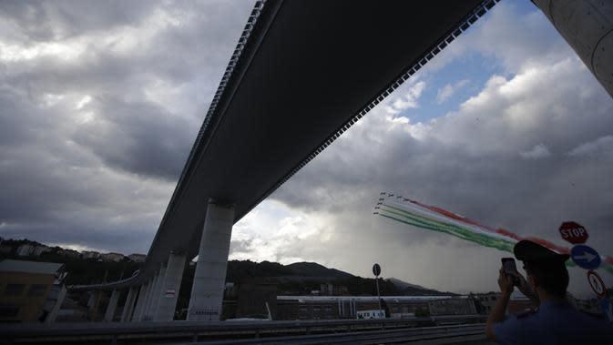 Tim aerobatik Angkatan Udara Italia, Frecce Tricolori (Panah Tiga Warna), terbang di atas Jembatan Saint George Genoa baru di Genoa, Italia, Senin (3/8/2020). Jembatan tersebut dibangun untuk menggantikan viaduk yang ambruk dua tahun lalu dan menewaskan 43 orang. (Xinhua/Stringer)