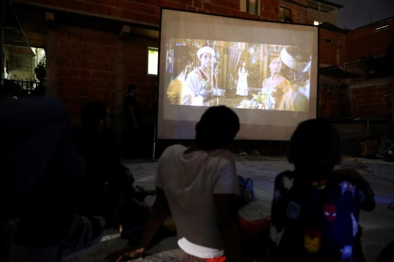 Children watch a movie projected on a giant screen for people to watch from their windows in the low-income neighborhood of Petare, amid the coronavirus disease (COVID-19) outbreak in Caracas