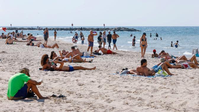 "Orang-orang bersantai di pantai di Tel Aviv, Israel, Minggu (18/10/2020). Israel ""dengan hati-hati"