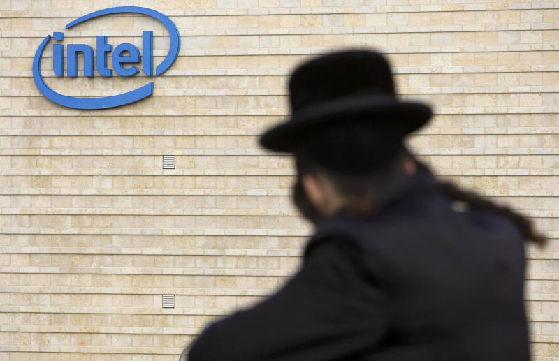 """FILE - In this Nov. 14, 2009 file photo, an ultra-Orthodox Jewish man is seen next to Intel's office building in Jerusalem. Intel said Monday, May 4, 2020, that it has purchased Israeli urban mobility startup Moovit for $900 million. The California-based chipmaker said the purchase buttresses its plan to become a """"complete mobility provider. (AP Photo/Bernat Armangue, File)"""