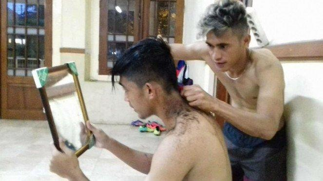 Gelandang Gresik United, M Sidik Saimmima (kanan), saat mencukur rambut Arsyad Yusgiantoro.