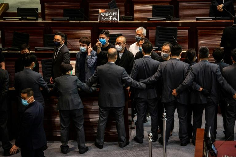 Protesting Hong Kong pro-democracy lawmakers (facing) are blocked by security (bottom) during debate on a law banning insulting China's national anthem