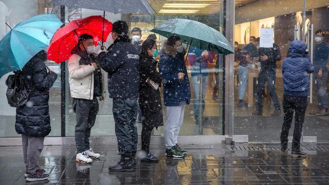 Petugas keamanan mengukur suhu tubuh pelanggan di luar Apple Store yang dibuka kembali di Beijing, China, Jumat (14/2/2020). Pembukaan kembali Apple Store ini dilakukan di tengah meningkat tajamnya korban tewas akibat virus corona di China. (AP Photo/Mark Schiefelbein)