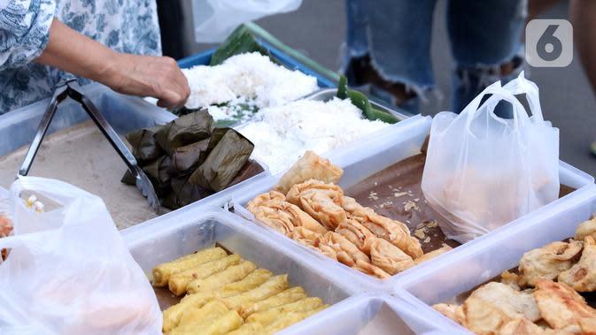 Pedagang menyiapkan makanan untuk berbuka puasa di kawasan Bendungan Hilir, Jakarta, Sabtu (25/4/2020). Meski ditengah pandemi virus Covid-19, masyarakat masih antusias berburu penganan berbuka puasa dengan tetap menerapkan pola jaga jarak dan memakai masker. (Liputan6.com/Helmi Fithriansyah)