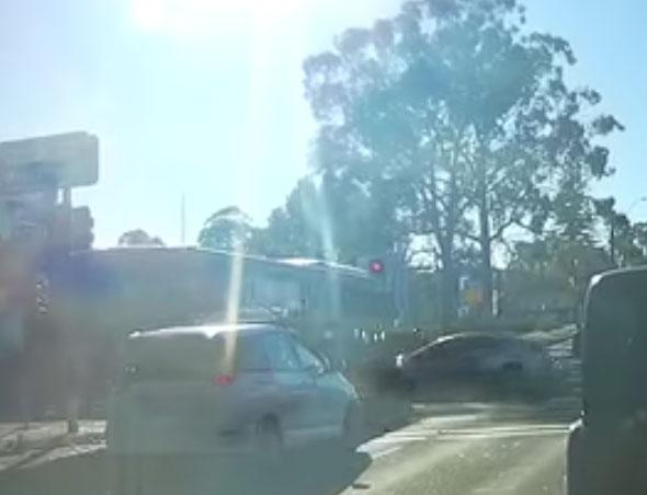 This still from dashcam footage shows a car smashing into a bus which ran a red light at an intersection.