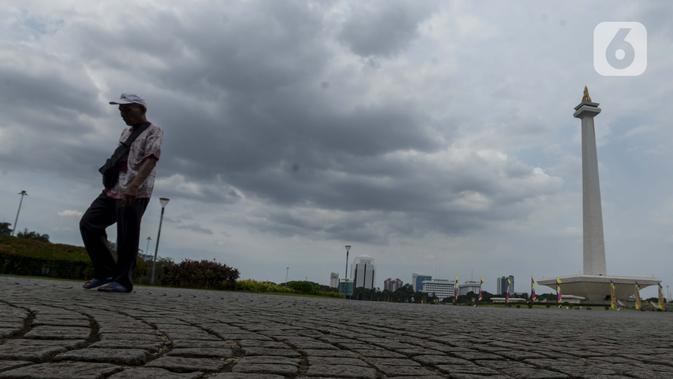 Pejalan kaki berjalan di kawasan Monumen Nasional (Monas) yang akan dijadikan arena lintasan balapan Formula E 2020, Jakarta, Selasa (11/2/2020). Formula E 2020 seri Jakarta akan memakai lintasan Monas untuk balapan mobil listrik Formula E pada 6 Juni 2020. (merdeka.com/Imam Buhori)
