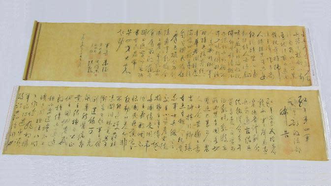 Dua lembar gulungan kaligrafi karya Mao Zedong dipajang di Hong Kong pada 6 Oktober 2020. Gulungan itu dipotong dua untuk memudahkan penyimpanan oleh seorang pembeli yang mendapatkannya hanya seharga sekitar Rp 950 ribu yang meyakini bahwa karya itu palsu . (Hong Kong Police Force via AP)