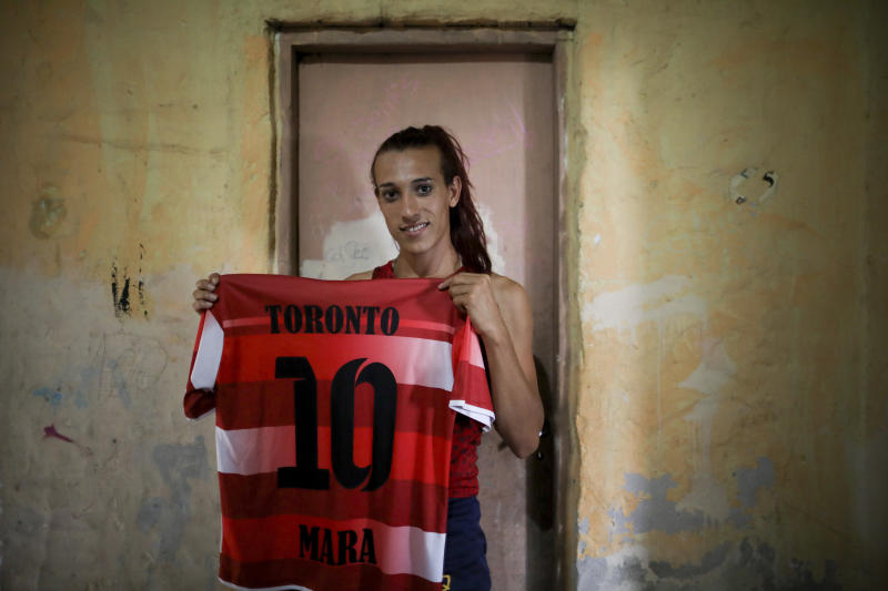Soccer player Mara Gomez poses with her old jersey from the first amateur soccer club she played for, Toronto, in La Plata, Argentina, Thursday, Feb. 6, 2020. Gomez is a transgender woman who is limited to only training with her women's professional soccer team, Villa San Carlos, while she waits for permission to start playing from the Argentina Football Association (AFA). If approved, she would become the first trans woman to compete in a first division, professional Argentine AFA tournament. (AP Photo/Natacha Pisarenko)