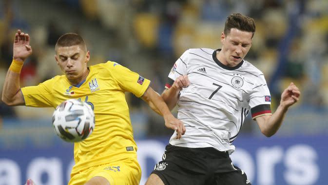 Gelandang Jerman, Julian Draxler berebut bola dengan bek Ukraina, Vitaliy Mykolenko pada pertandingan UEFA Nations League di Stadion Olimpiyskiy di Kyiv, Ukraina, Sabtu (10/10/2020). Jerman menang 2-1 atas Ukraina. (AP Photo/Efrem Lukatsky)