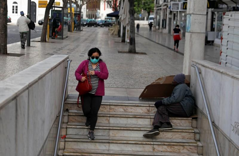A woman wearing a protective mask as a preventive measure against coronavirus disease (COVID-19) enters the subway at Rossio Square in downtown Lisbon